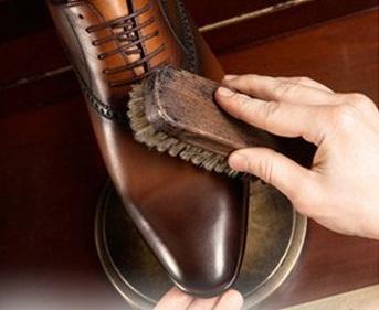 Ciabattino che pulisce scarpe